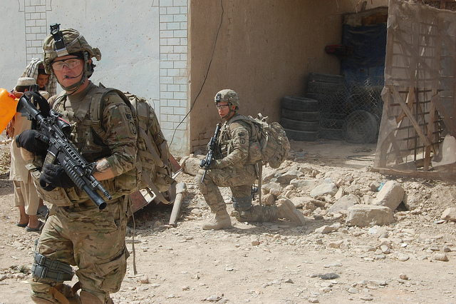 Sgt. Chris Coats and Pfc. William Westmeyer, 561st Military Police Company, attached to 2nd Brigade Combat Team, 4th Infantry Division, pull security outside an open-air market in subdistrict 9 of Kandahar City, July 30. Coats' team conducted random searches of businesses in the area to identify possible improvised explosive device cells.
